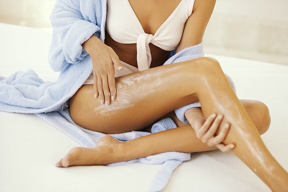 WOMAN APPLYING LOTION TO LEGS, CLOSE UP
